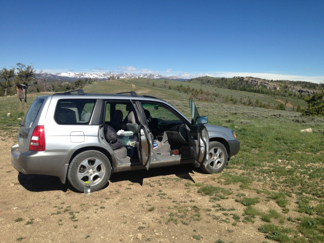 "Matt's Subaru in the ""parking area"" of Wild Iris. You can see the Wind River Range on the horizon."