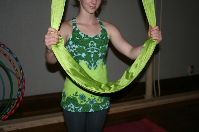 The aerial yoga silk is one long piece of fabric that hangs from one point above